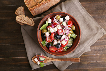 Greek salad served in brown bowl with bread