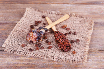 Spoons with coffee beans on sackcloth on blue wooden background
