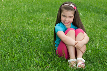 Little girl sits on the grass