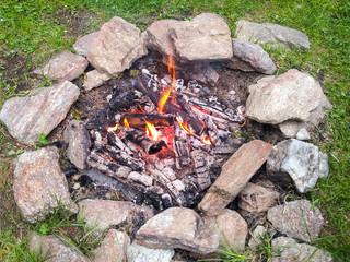 Brennendes Lagerfeuer auf einer Wiese umrandet von Steinen