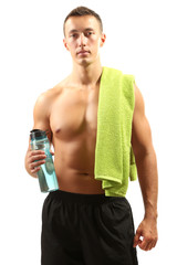 Handsome young muscular sportsman holding towel and bottle with