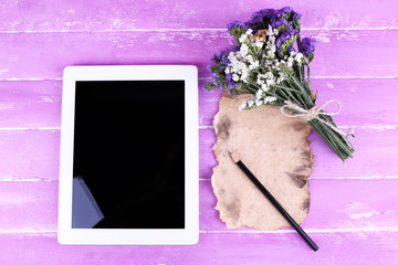 Tablet, bunch of flowers and piece of paper and pencil