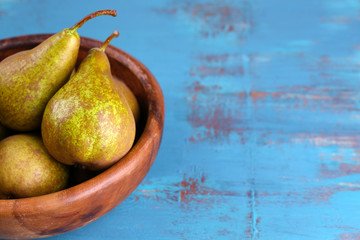 Ripe pears in bowl, on color wooden background