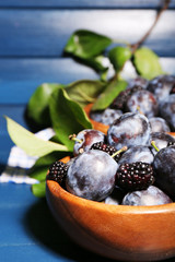 Ripe sweet plums in bowls, on wooden table