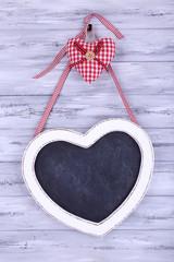 Heart shaped chalkboard on wooden background