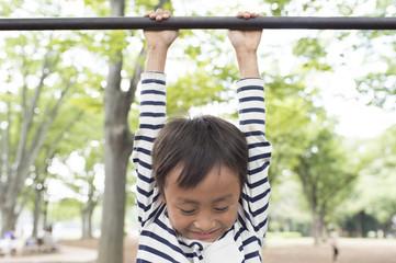 Boy hanging on horizontal bar