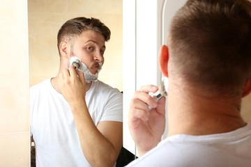 Young man shaving his beard in bathroom