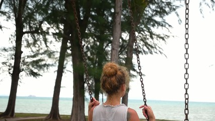 Serene Girl on a Swing in Park with Seascape. Slow Motion.