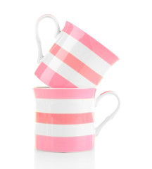Pink and white ceramic mugs isolated on white