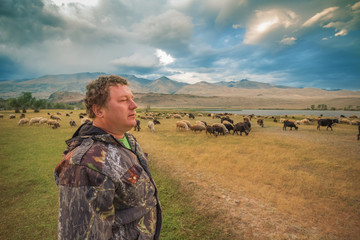A man and a herd of goats and sheep