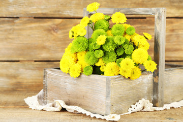 Yellow and green flowers in basket on wooden background