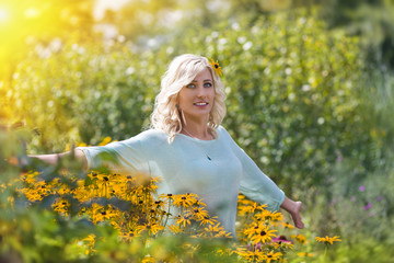 Young woman in the field with flowers under sun