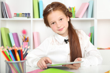 Cute girl with tablet at workplace in classroom