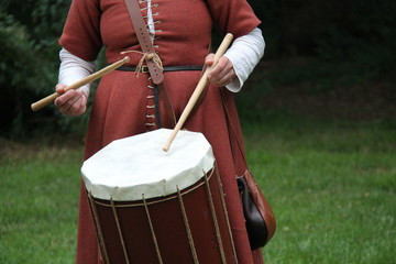 A Lady in Costume Playing a Medieval Style Drum.