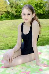 Teenager in Badeanzug auf Liegewiese in Freibad