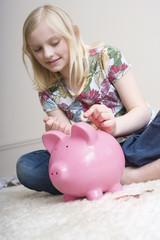 Mädchen (8-9),die Geld im Sparschwein,Portrait