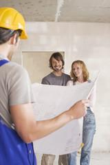 Bauarbeiter Halte Bauplan,junges Paar im Hintergrund
