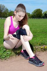 Joggerin legt Bandage um Knie-Gelenk