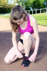 Läuferin schnürt Schuhe für Lauf-Training