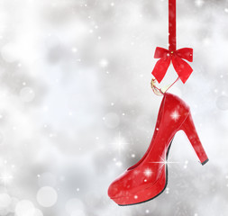 High heel shoe hanging on red ribbon