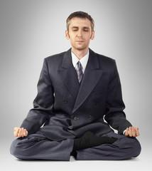 Meditating businessman sitting on the floor
