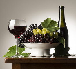 Red wineglass of red wine on the wooden table with grapes