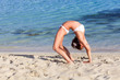 A woman is doing exercises on the beach