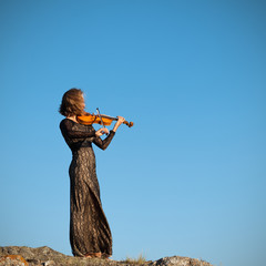 Girl in concert dress, playing the violin