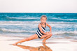 Beautiful little girl excercising on the beach