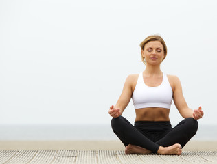 Young woman sitting outdoors in yoga pose