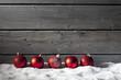canvas print picture - Rote Weihnachtskugeln auf Schneehaufen, Holzwand als Hintergrund