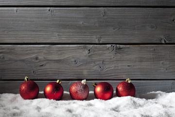 Rote Weihnachtskugeln auf Schneehaufen, Holzwand als Hintergrund