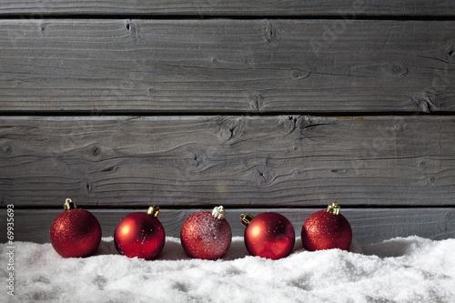 canvas print picture Rote Weihnachtskugeln auf Schneehaufen, Holzwand als Hintergrund