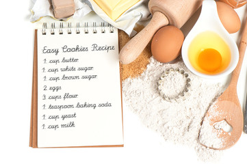 recipe book and baking ingredients eggs, flour, sugar, butter, y