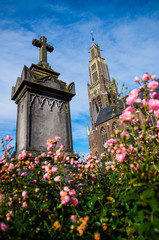Tombstone with pink roses and church in background