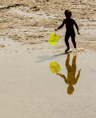Niño jugando con caldero en la playa