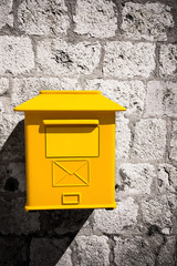 Yellow mailbox on stone wall