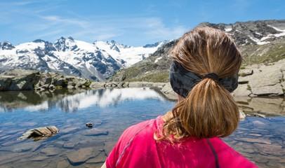 Young woman watching mountain lake