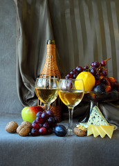 Two glasses of wine, cheese and ripe fruit.