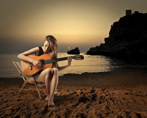 young girl playing guitar at sunset