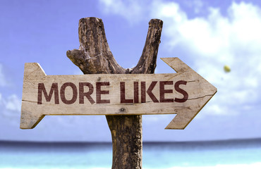More Likes wooden sign with a beach on background