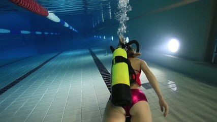 Female diver swimming underwater in the pool