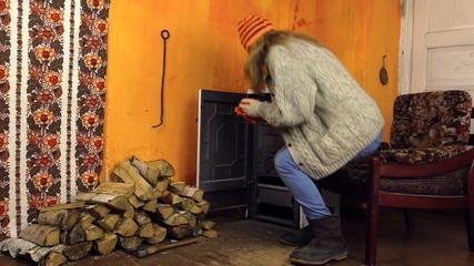 girl open oven door bask sitting in chair by fire in rural room