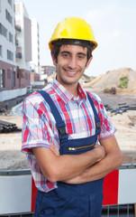Lachender Bauarbeiter mit verschränkten Armen auf der Baustelle