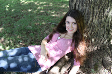 Young Brunette Laying Against Tree