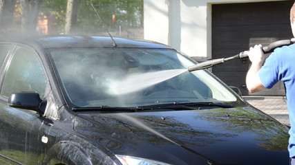 Worker man wash car windscreen with strong pressure water jet