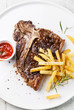 T-Bone Steak with Salted french fries on white plate on blue woo