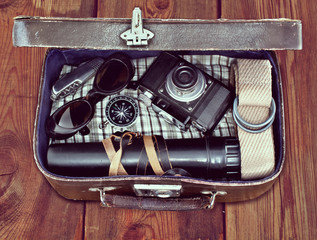 outdoor retro suitcase with things the traveler on the wooden fl