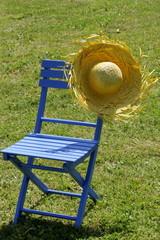 Blauer Stuhl mit Strohhut