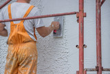 Plasterer applying a finish coating to a wall - 69944848